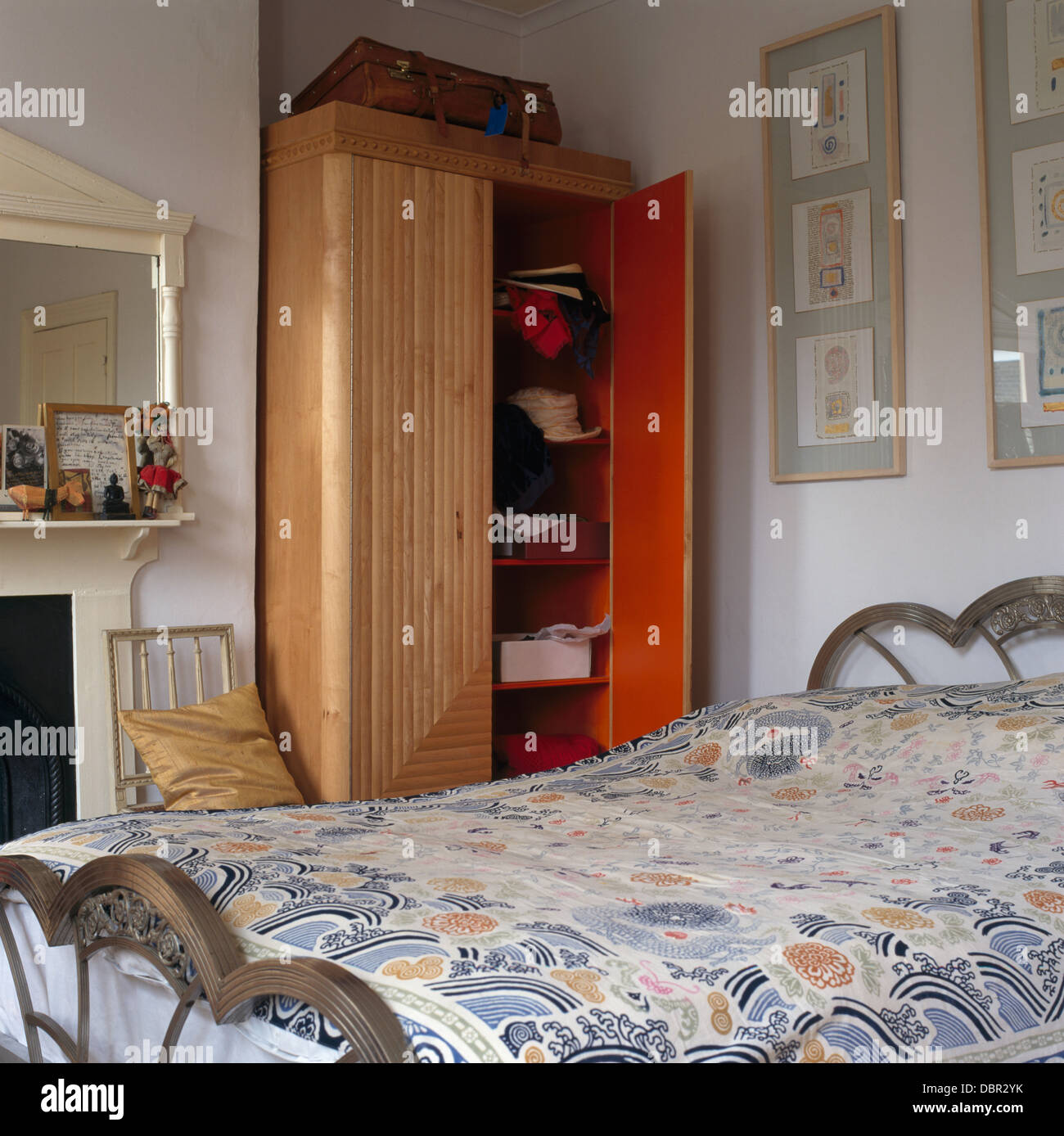 Wardrobe In Alcove Beside Fireplace In Small Bedroom With Patterned Duvet  On Metal Bed