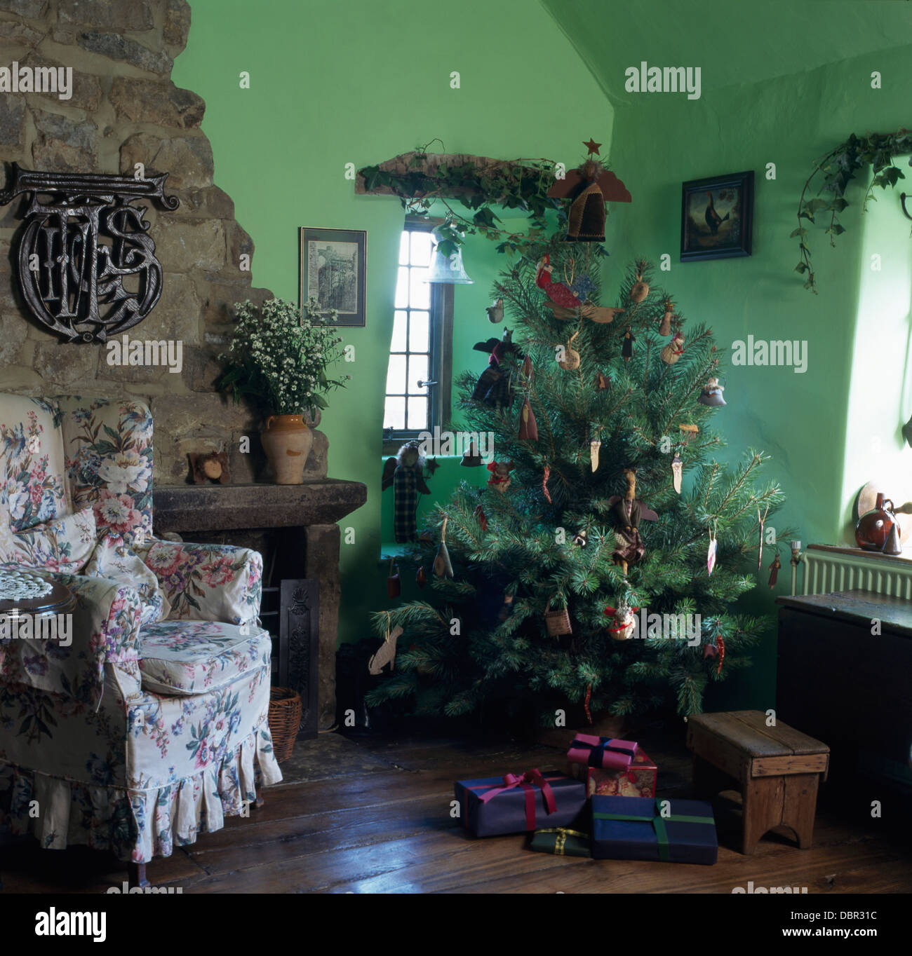 Christmas Tree In Corner Of Green Cottage Living Room With Wooden Stock Photo Alamy