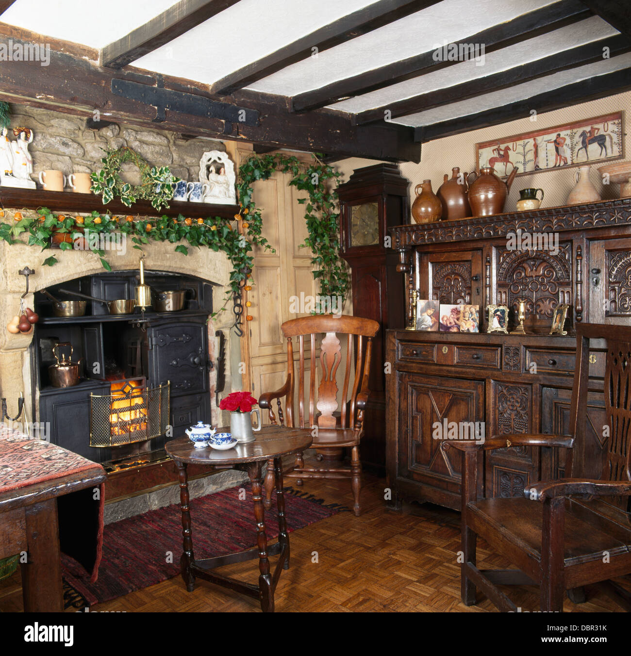 Ivy Christmas garland above old range in country dining room with Jacobean-style carved wood dresser and chair Stock Photo