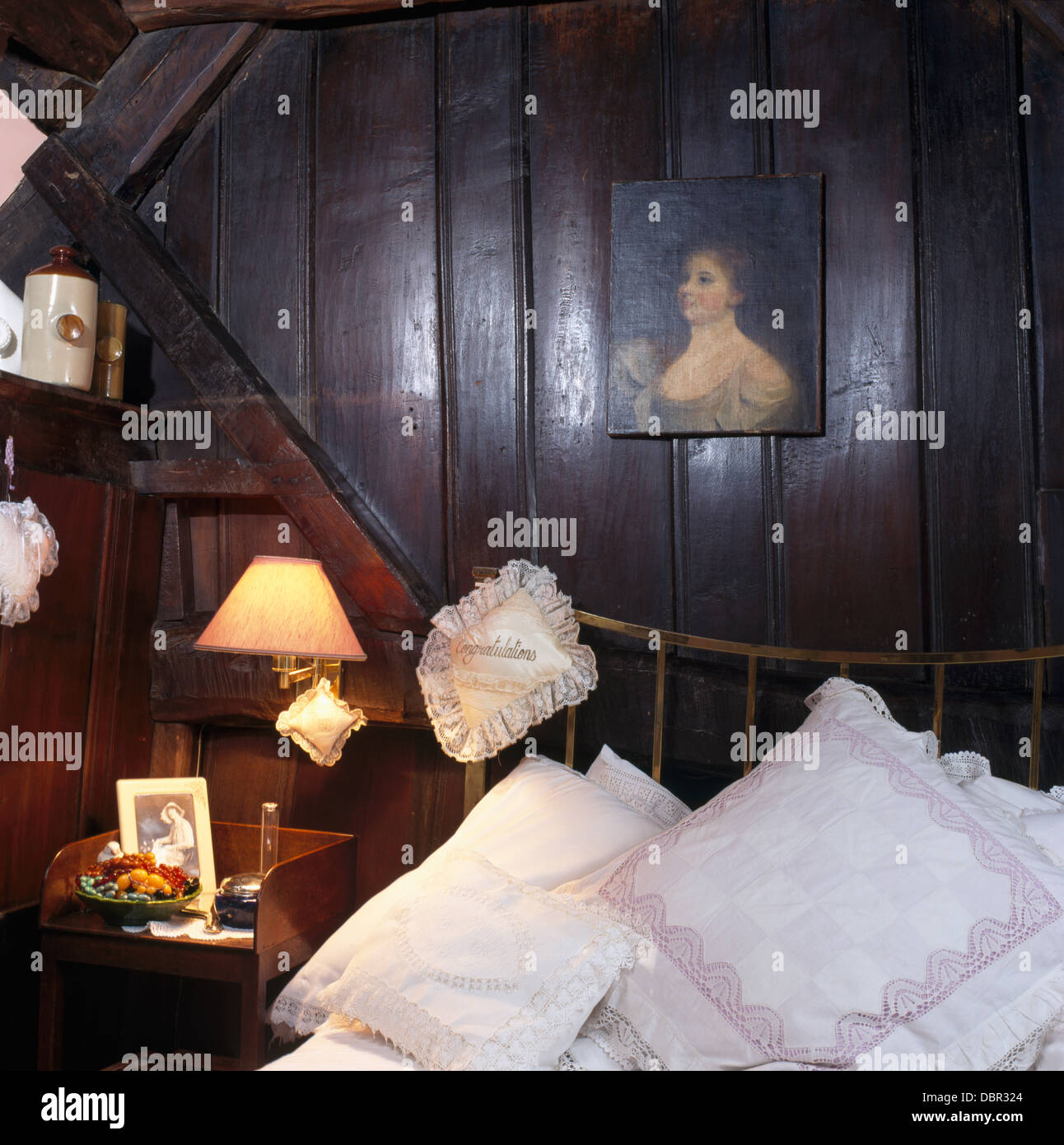 Small Painting On Dark Wood Paneling Above Bed Piled With White Stock Photo Alamy