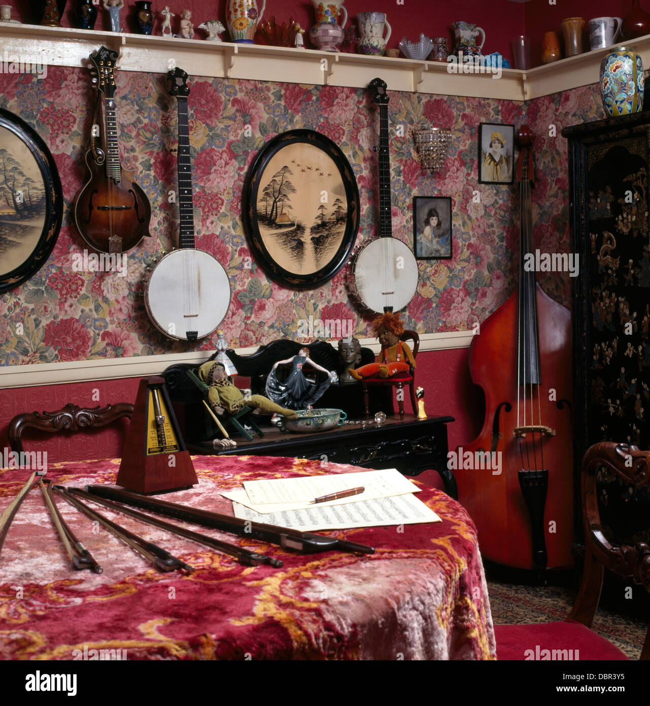 Collection of banjos on walls of small music room with dado rail and table with patterned red velvet cloth and double - Stock Image