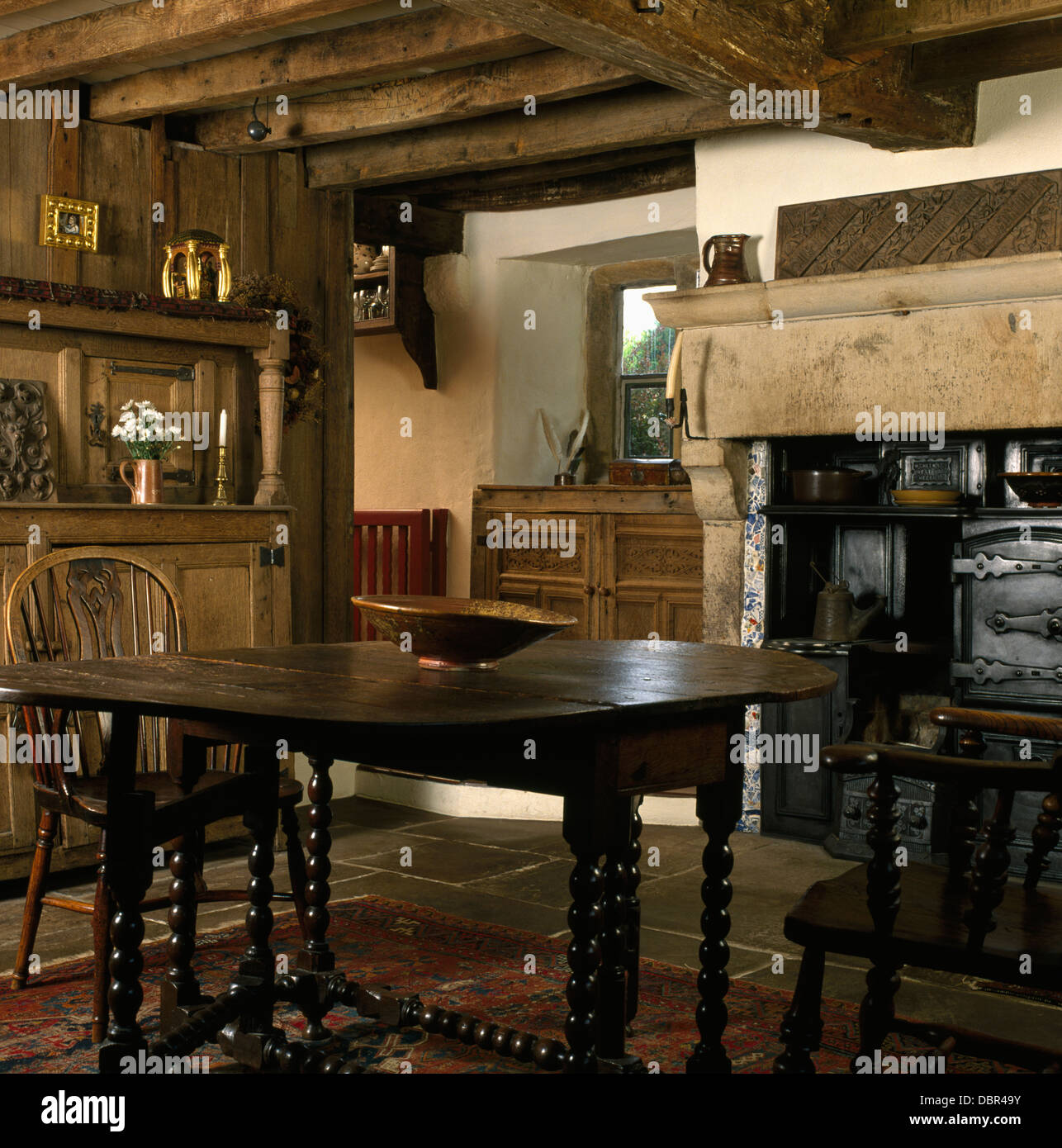 Windsor chairs and Jacobean oak table with barley-twist legs in beamed country dining room with old cast-iron range Stock Photo