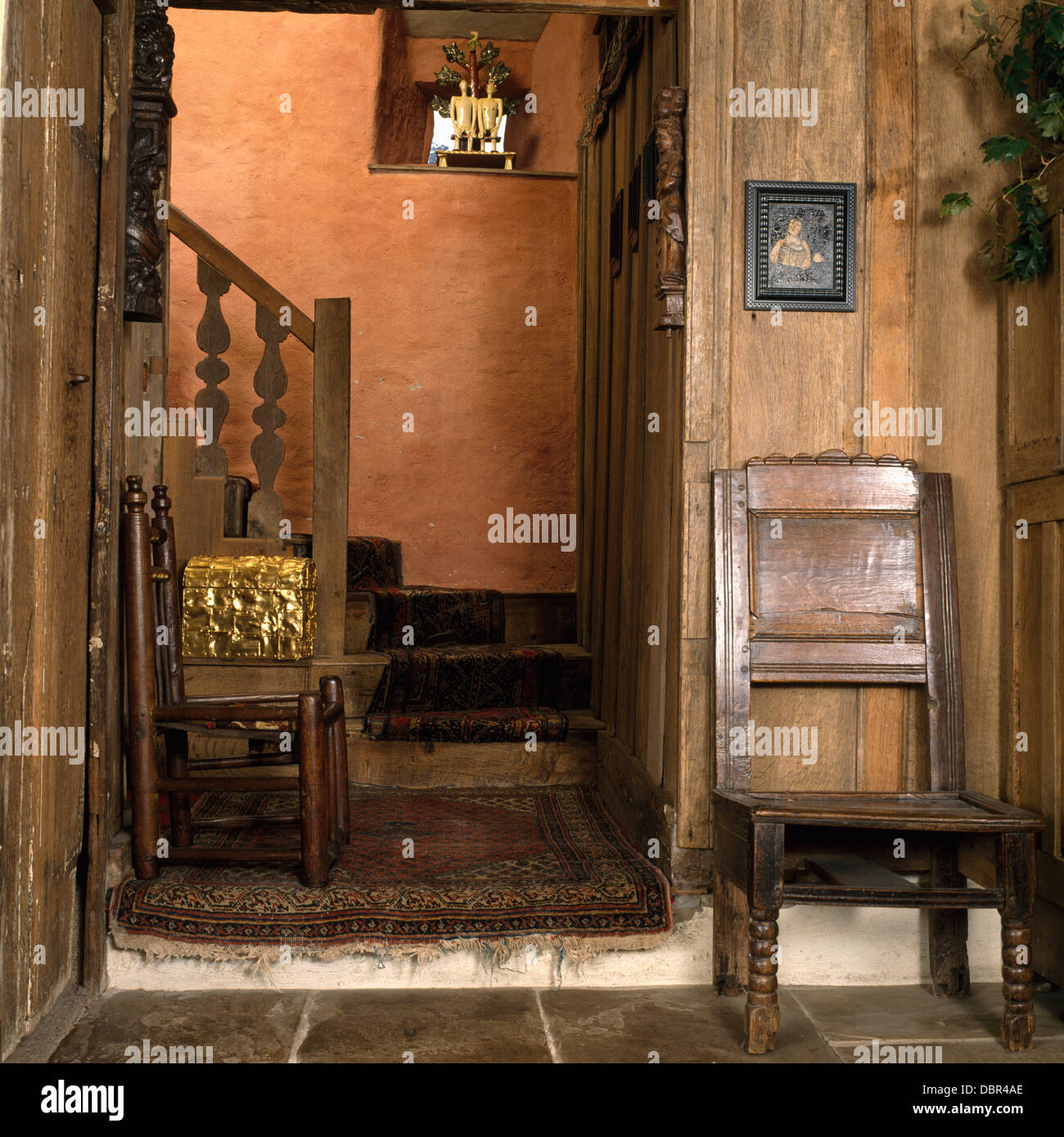 Antique oak chairs in oak paneled hall with oak staircase Stock Photo