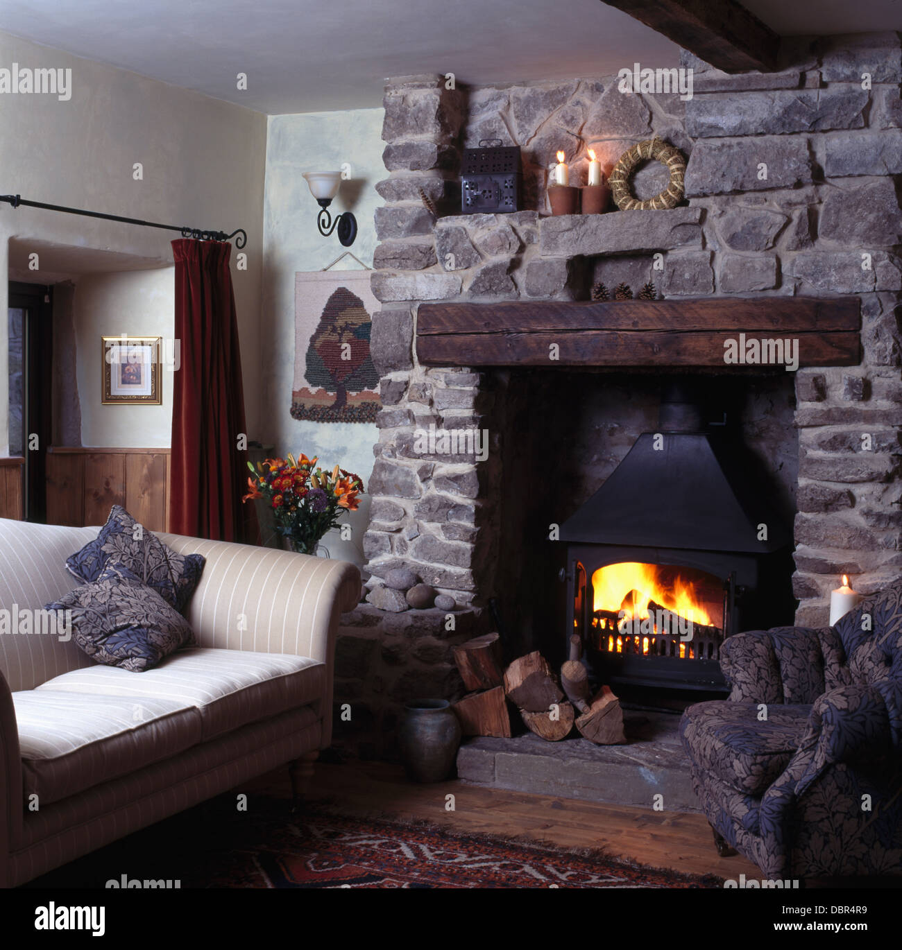 Small Beige Sofa Beside Fireplace With Lighted Wood