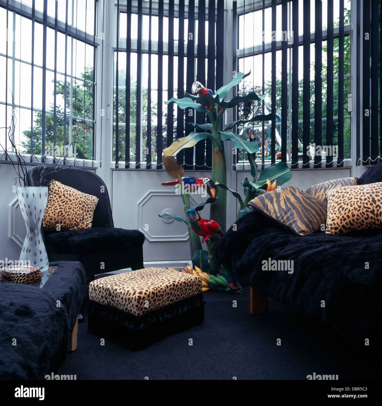 Animal Print Cushions On Black Armchairs And Sofa In Front Of Window With  Black Venetian