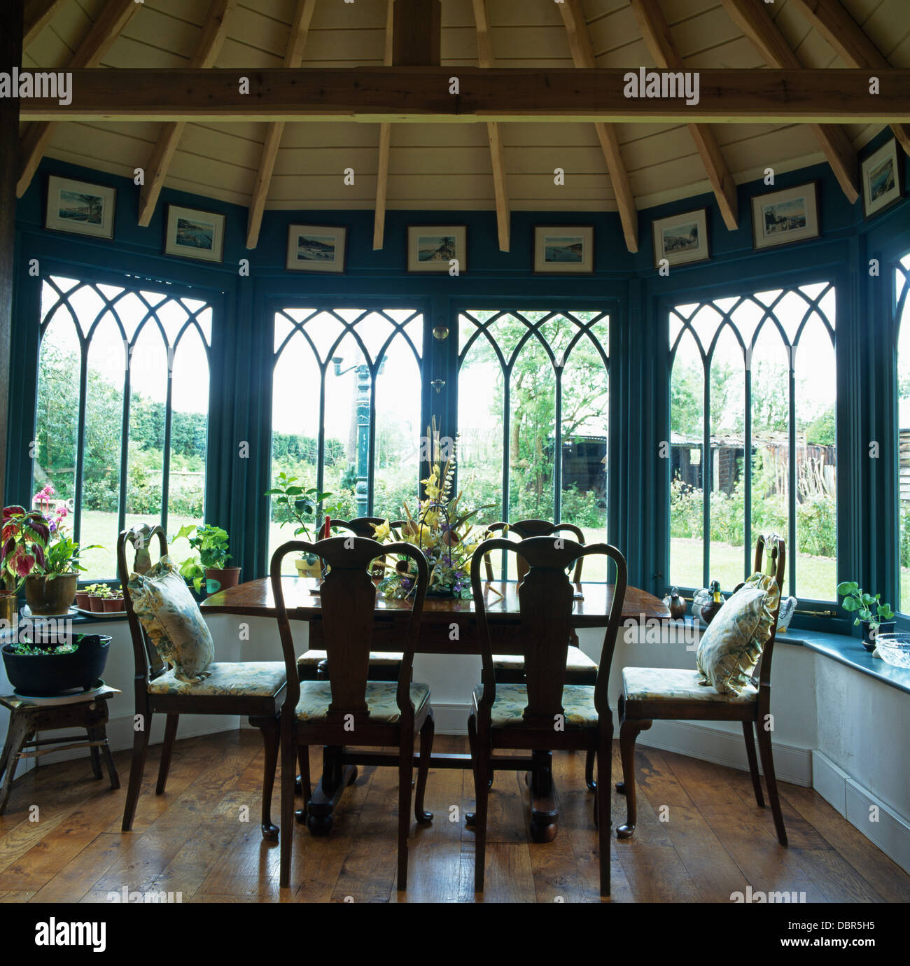 Antique table and chairs in front of bay window in dining room with wooden  floor and ceiling in newly-built Tudor-style house - Antique Table And Chairs In Front Of Bay Window In Dining Room With