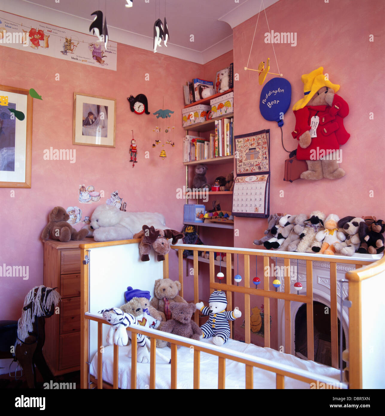 soft toys in baby s cot in pink nursery bedroom with large felt