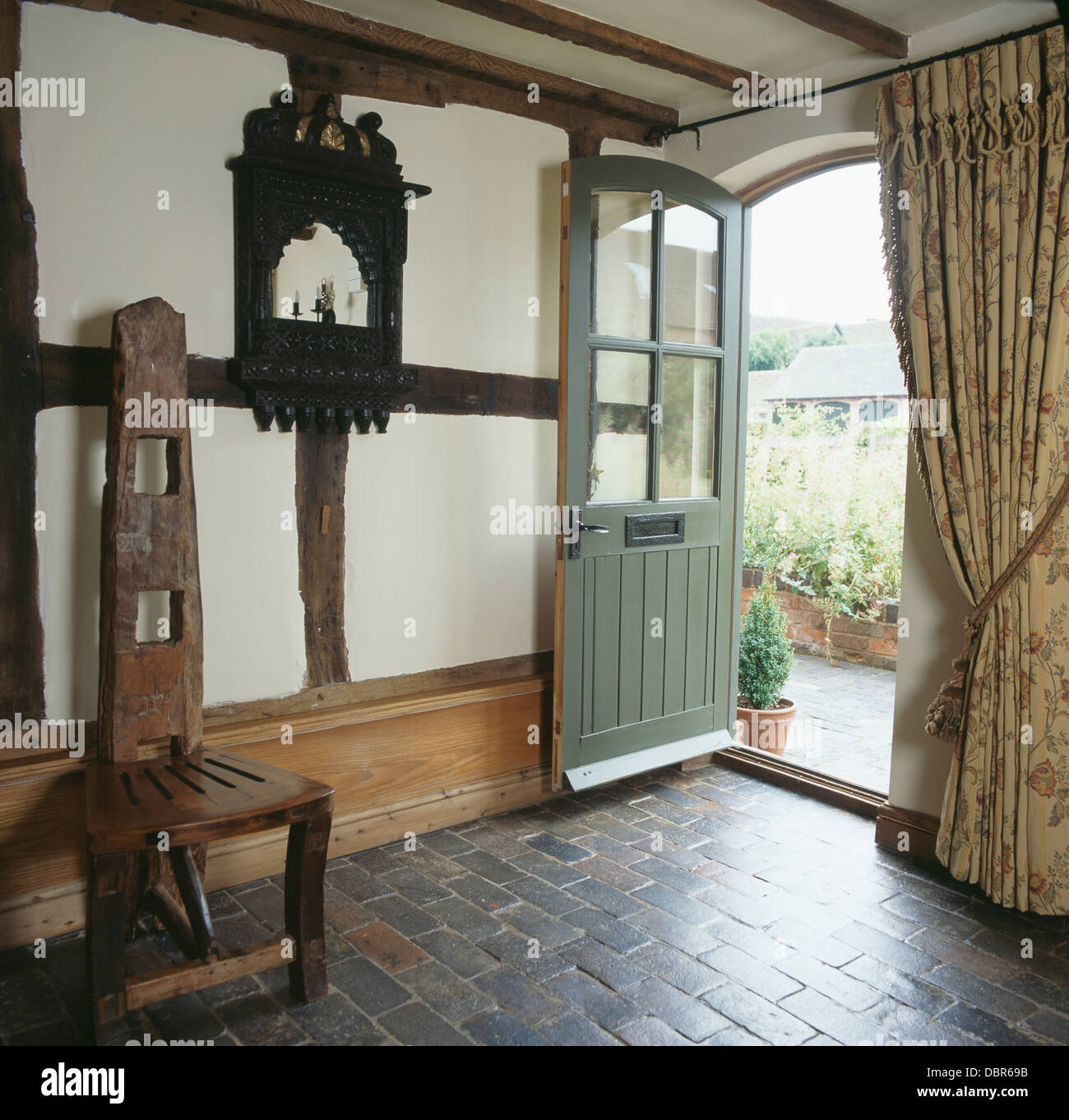 Tall Back Hand Crafted Wooden Chair And Gray Brick Flooring In Cottage Hall  With Heavy Curtain Beside Open Front Door