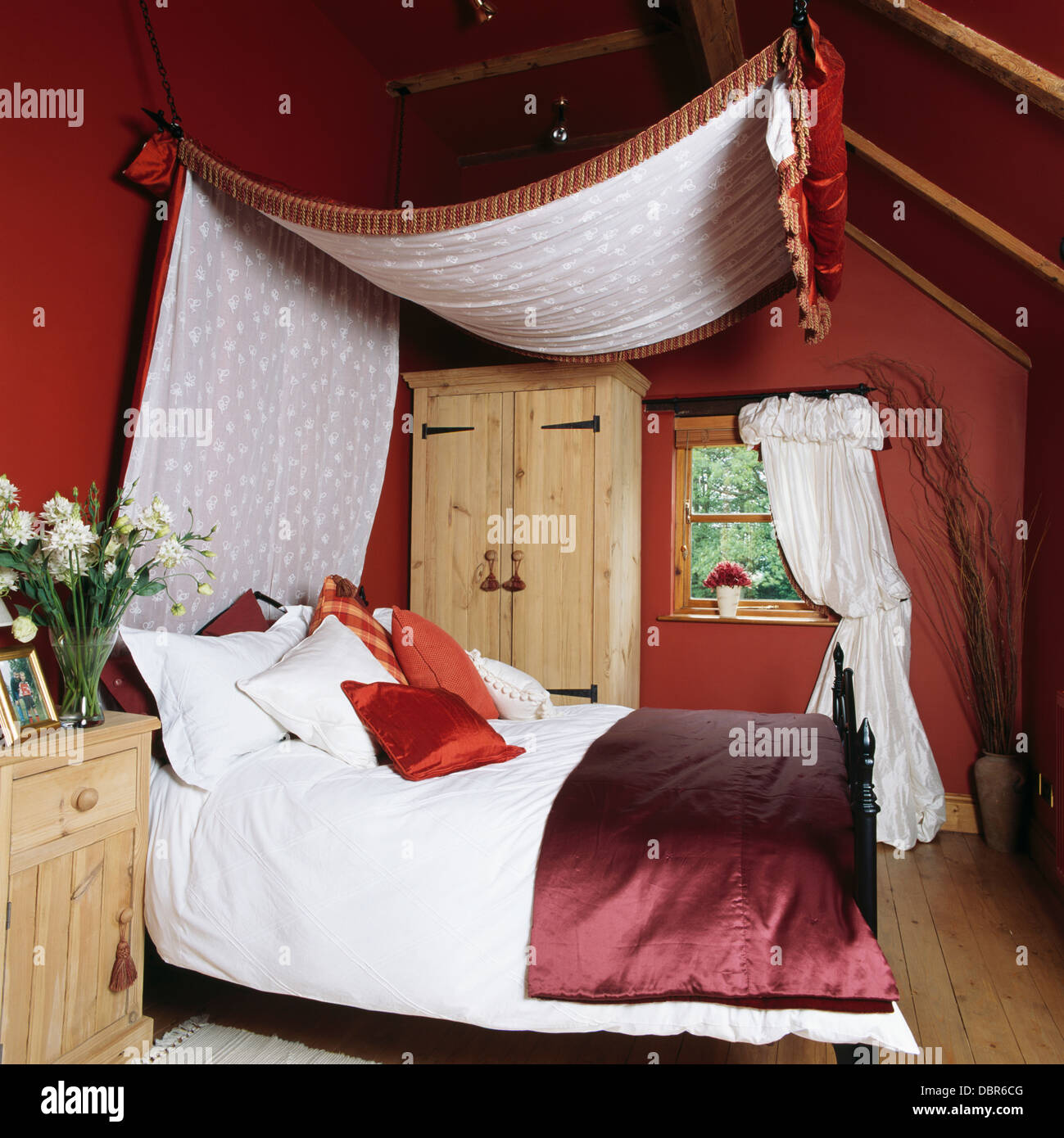 canopy with white voile lining above bed with white duvet and red satin throw in red attic bedroom in country cottage