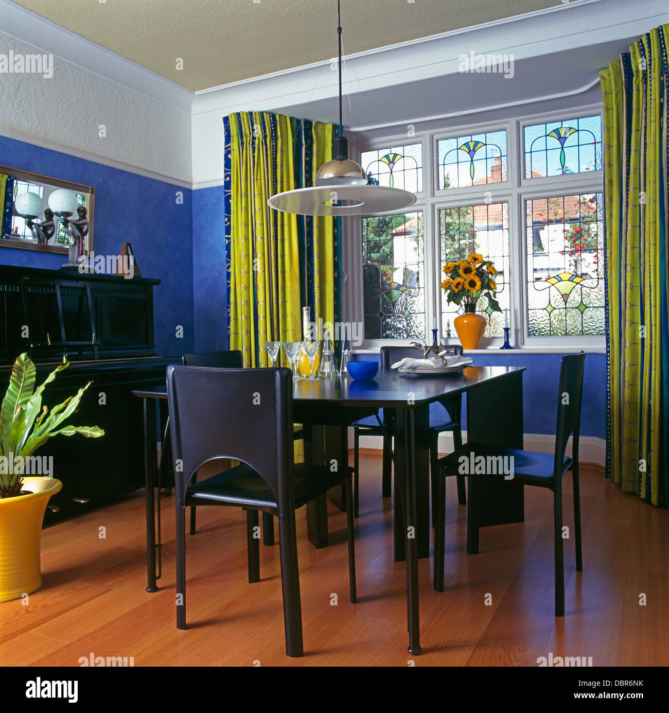 Disc Light Above Black Chairs And Table In Modern Blue Dining Room With  Lime Green Curtains On Stained Glass Windows