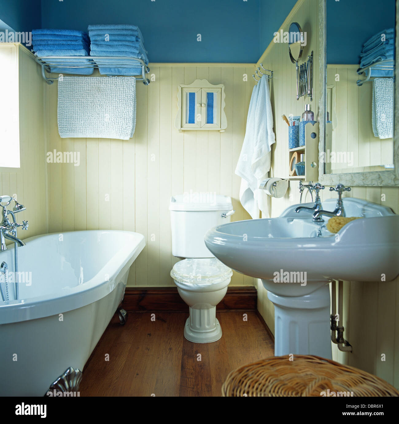 Claw-foot bath in blue bathroom with blue towels on chrome shelf on ...