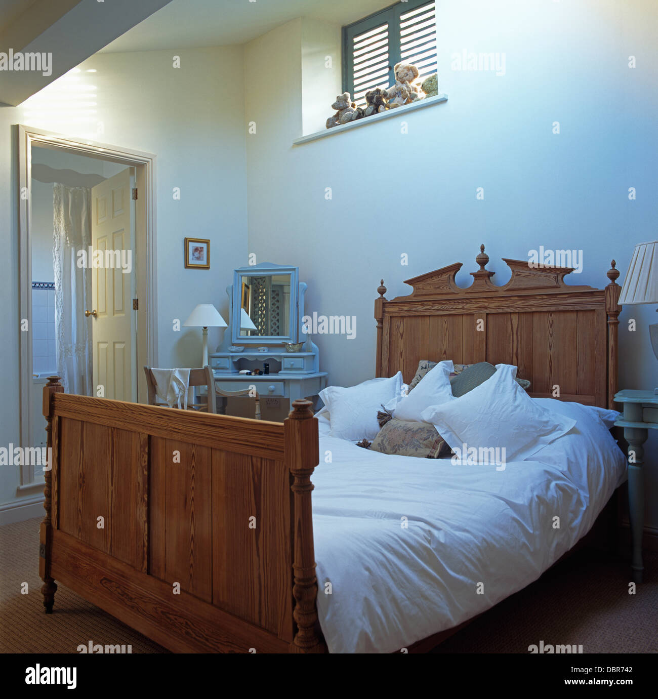 White Duvet And Pillows On Old Pine Bed With Ornate Headboard In Modern Bedroom En Suite Bathroom