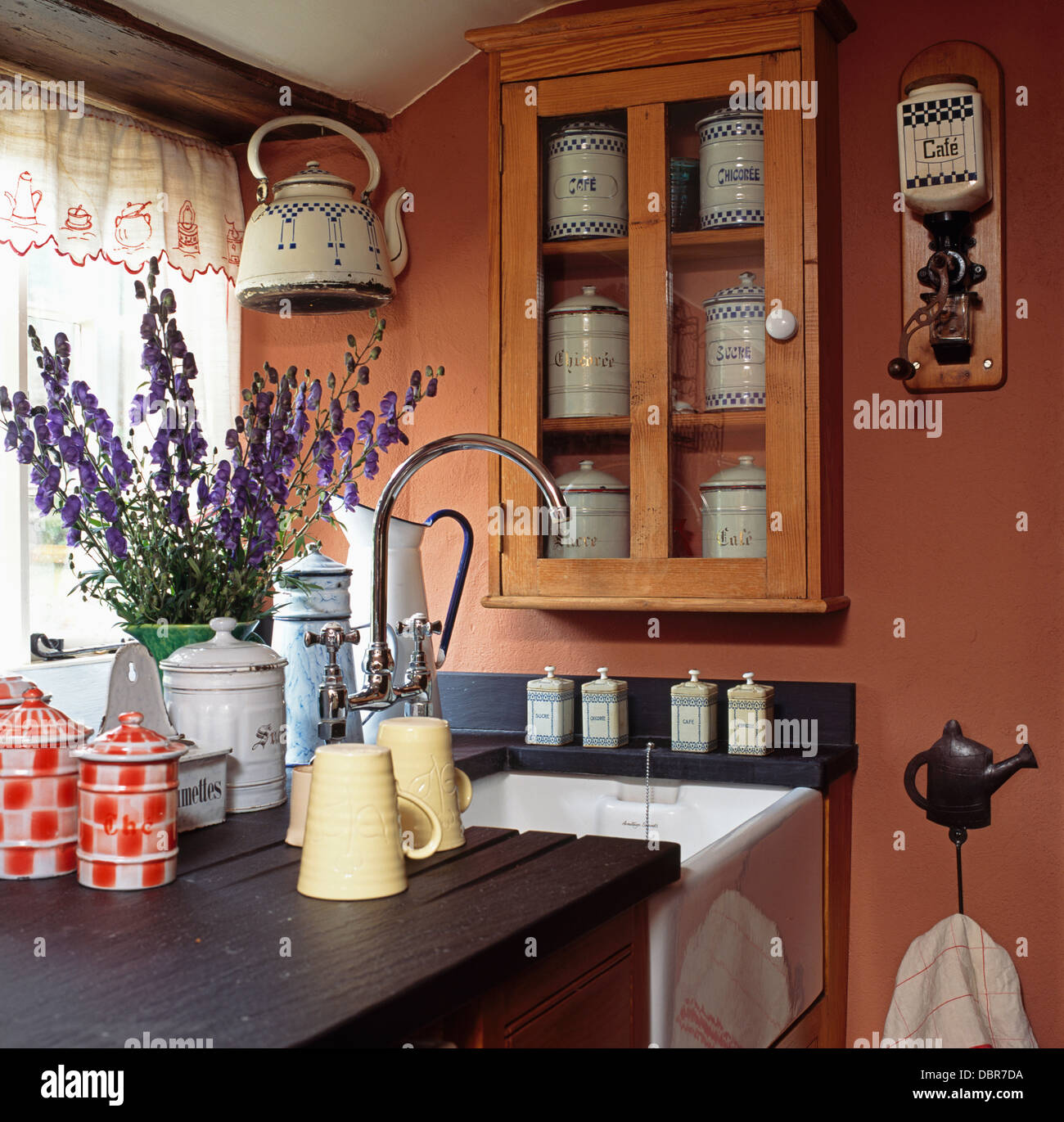Vintage enamel storage jars and jugs on draining board beside Belfast sink in terracotta painted kitchen with wall - Stock Image