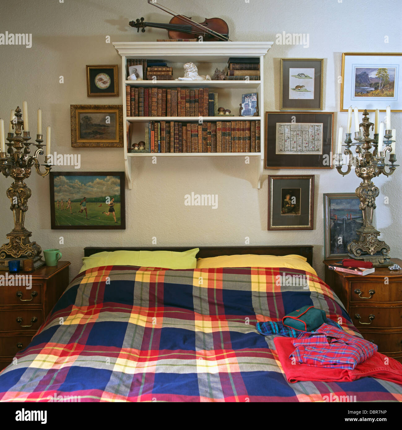 Old books on shelves above bed with colorful checked duvet and yellow pillows in country bedroom with candelabra on side tables