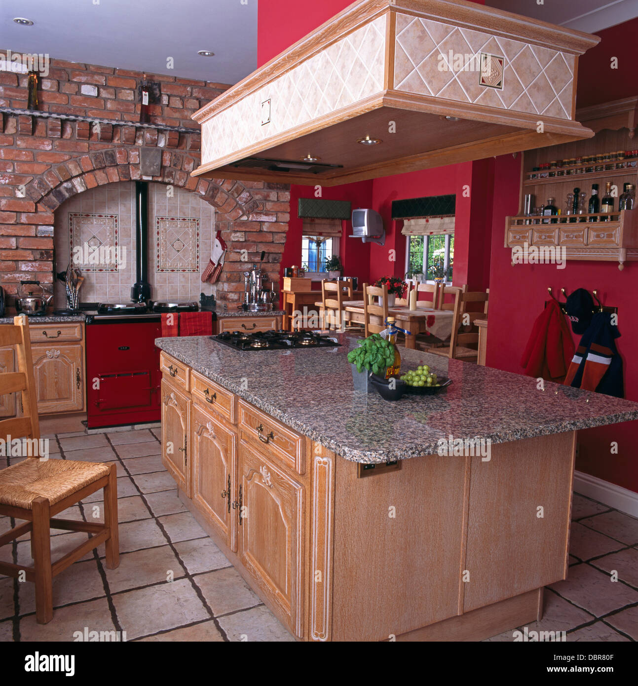 Wood Extractor Hood Above Island Unit With Granite Worktop In Red Country  Kitchen With Red Aga And Tiled Floor