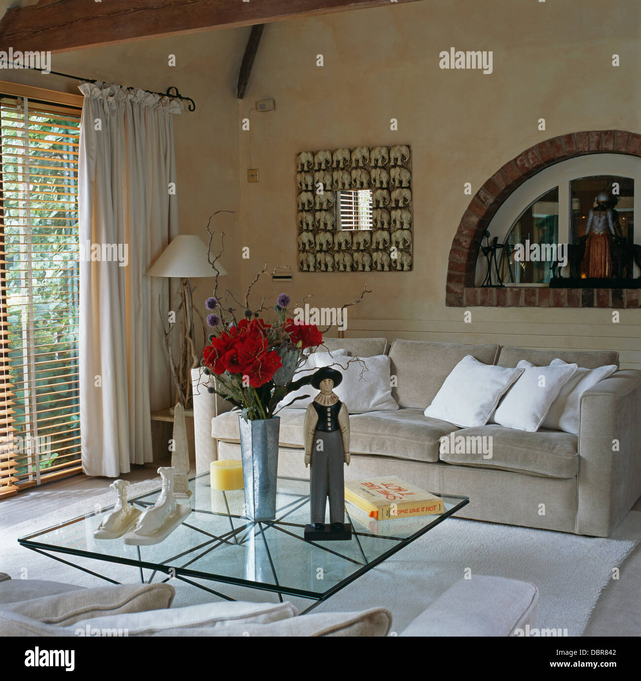 Wooden Figure And Vase Of Red Roses On Glass Coffee Table In Modern Living Room With Gray Velour Sofa Cream Curtains