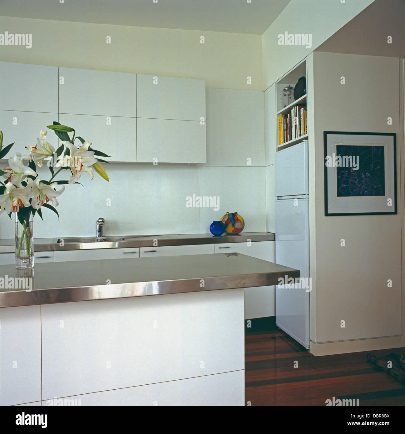 Stainless steel worktop on island unit in modern white urban kitchen ...