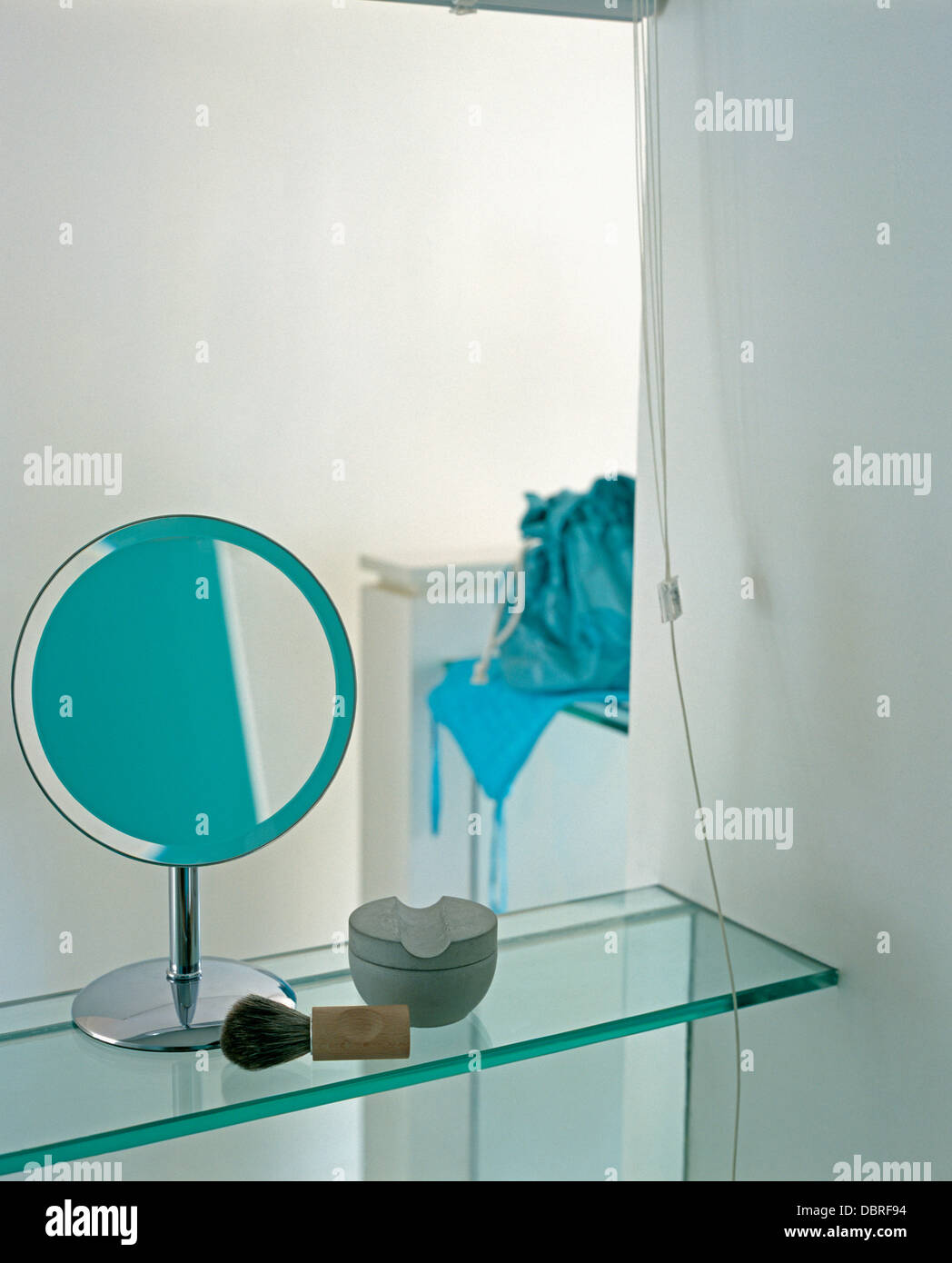 Close-up of small mirror on stand on glass shelf with shaving brush ...