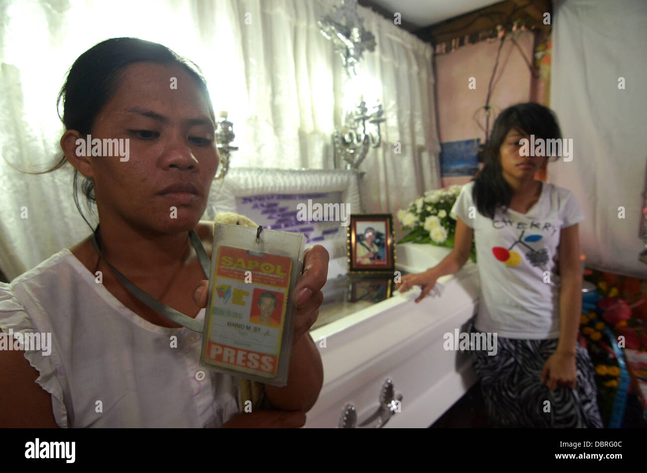 General Santos city, Southern Philippines. 3rd August, 2013. Mario Sy's Wife Violeta Sy (L) show press ID of Husband Stock Photo
