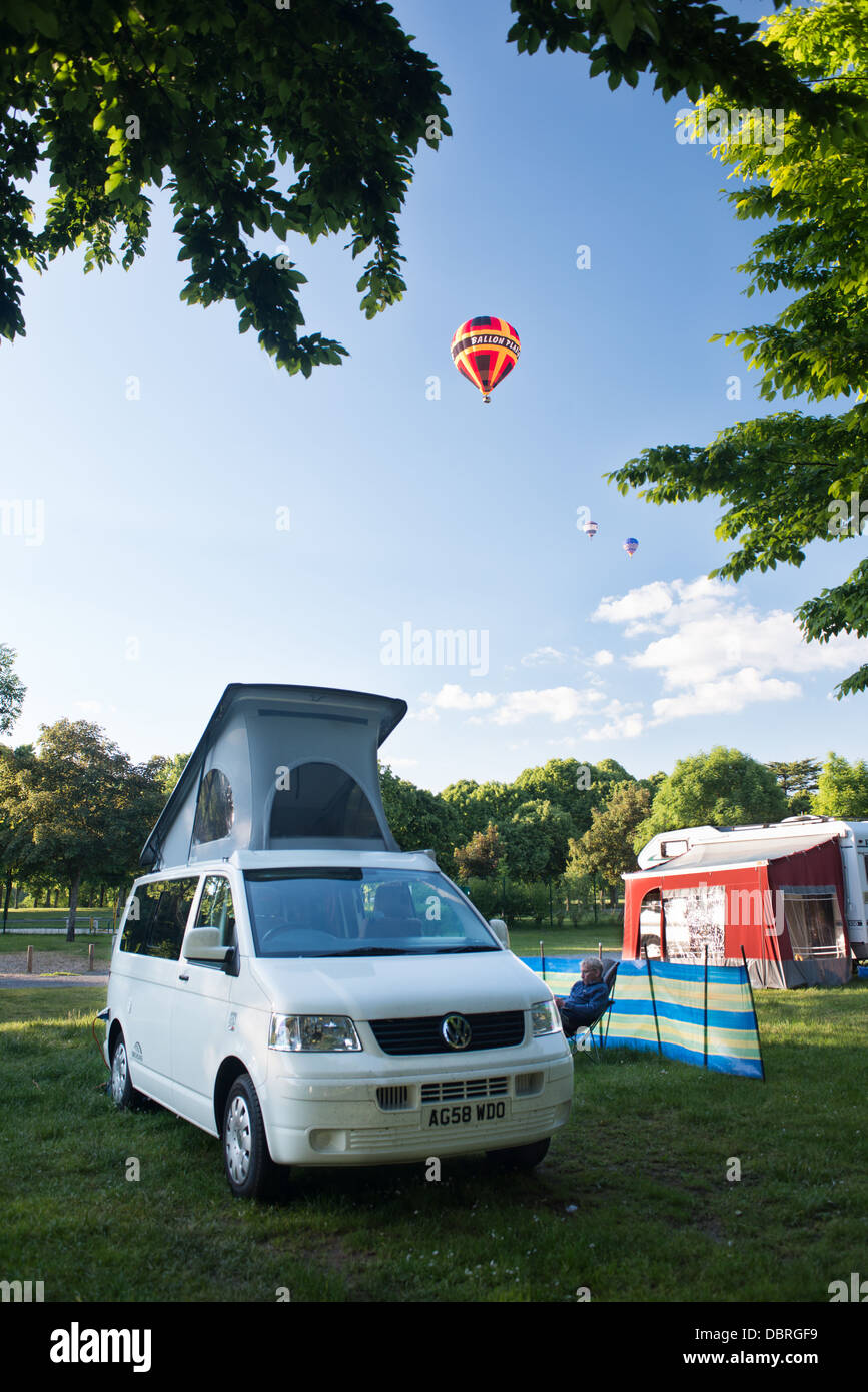 A brightly coloured hot air balloons flying above a campsite with and a VW camper van pitched up on a peaceful summer - Stock Image