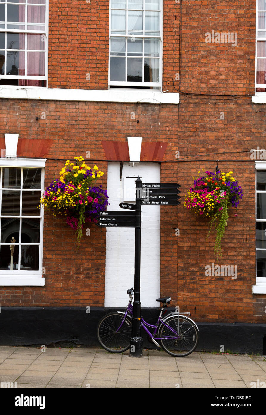 House in Warwick with parked bicycle and hanging baskets - Stock Image