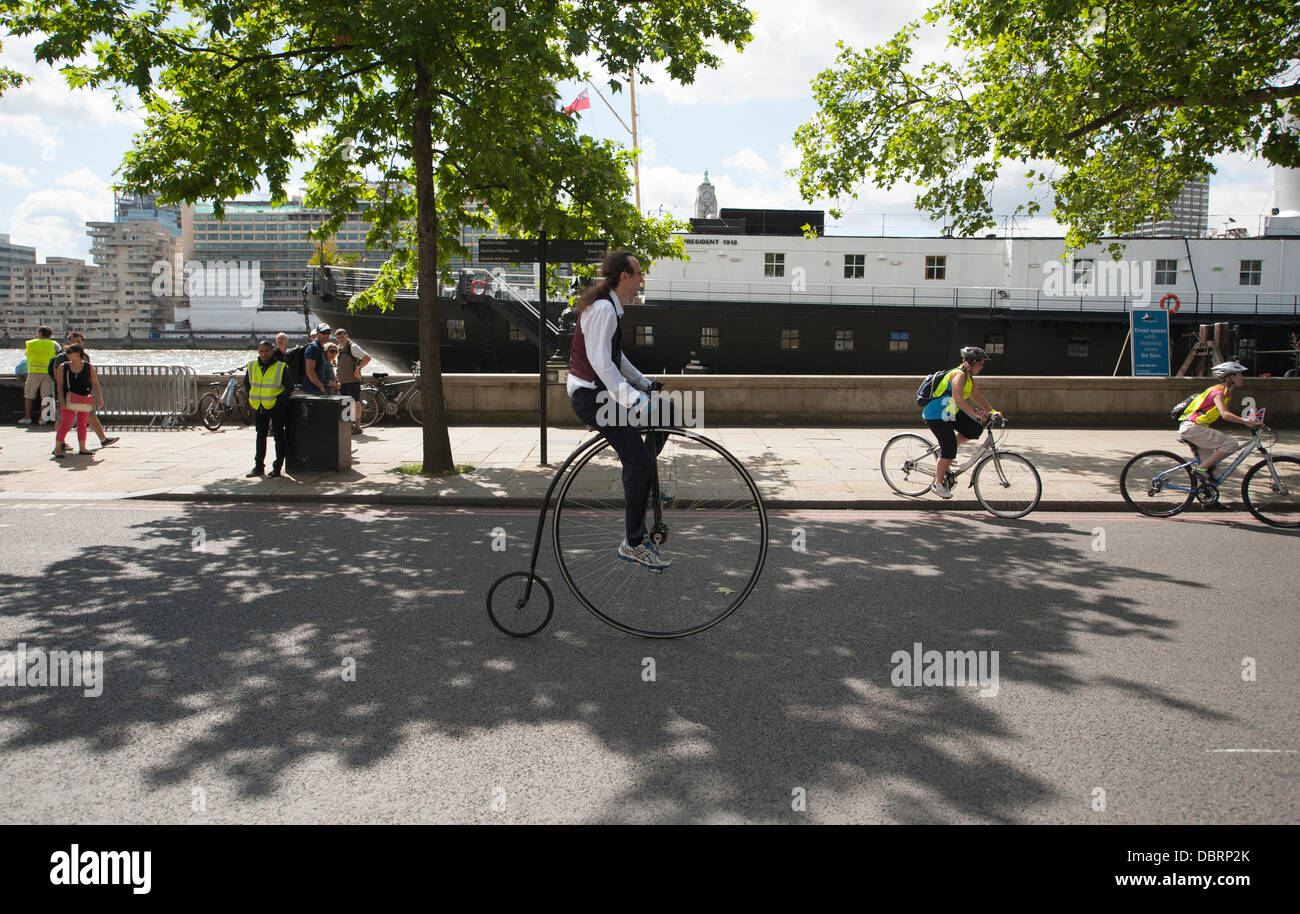 London, UK. 03rd Aug, 2013. Participant in the Freecycle event for everyone rides a penny farthing along The Embankment - Stock Image