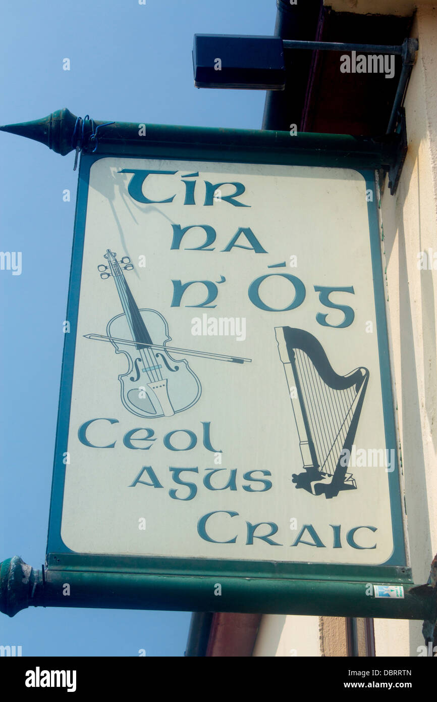 Tir Na nOg pub sign with Irish harp and fiddle and 'Ceol agus craic' ('Music and Fun') County Galway - Stock Image