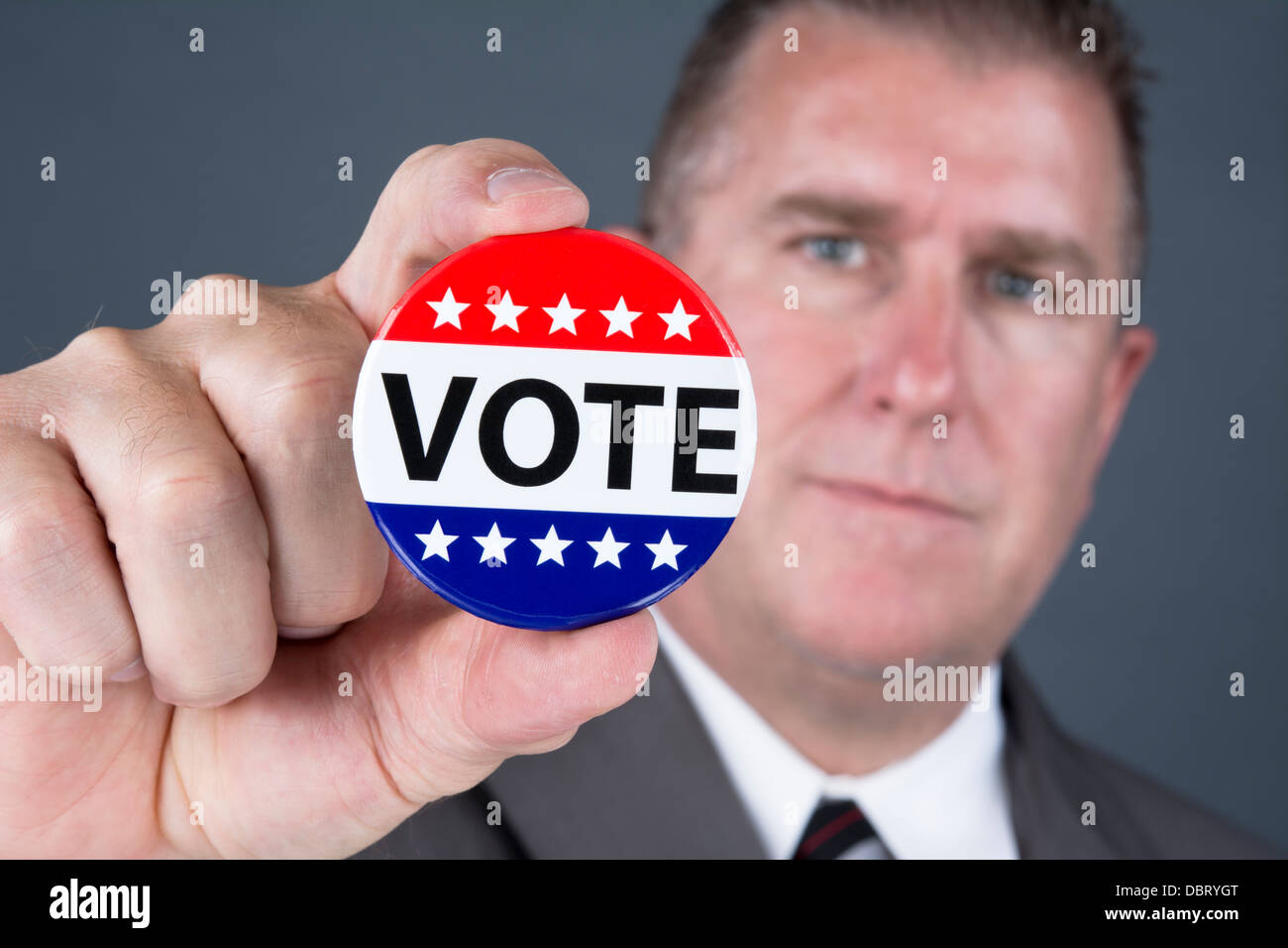 A male voter holds up a vote pin to promote democratic elections in the United States - Stock Image
