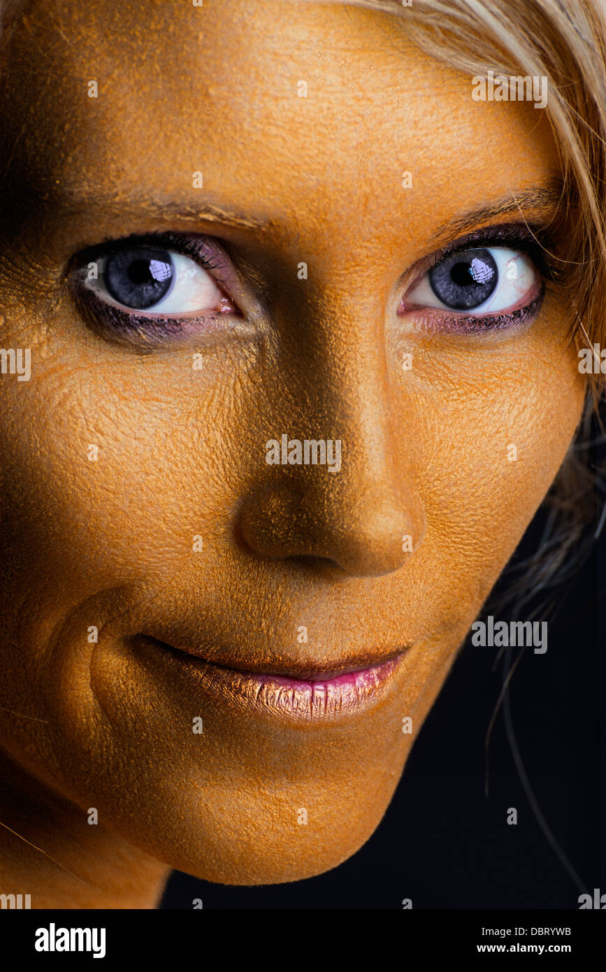 Frau mit Goldfarbe bemalt - Woman bodypainted with golden dye.  - Stock Image