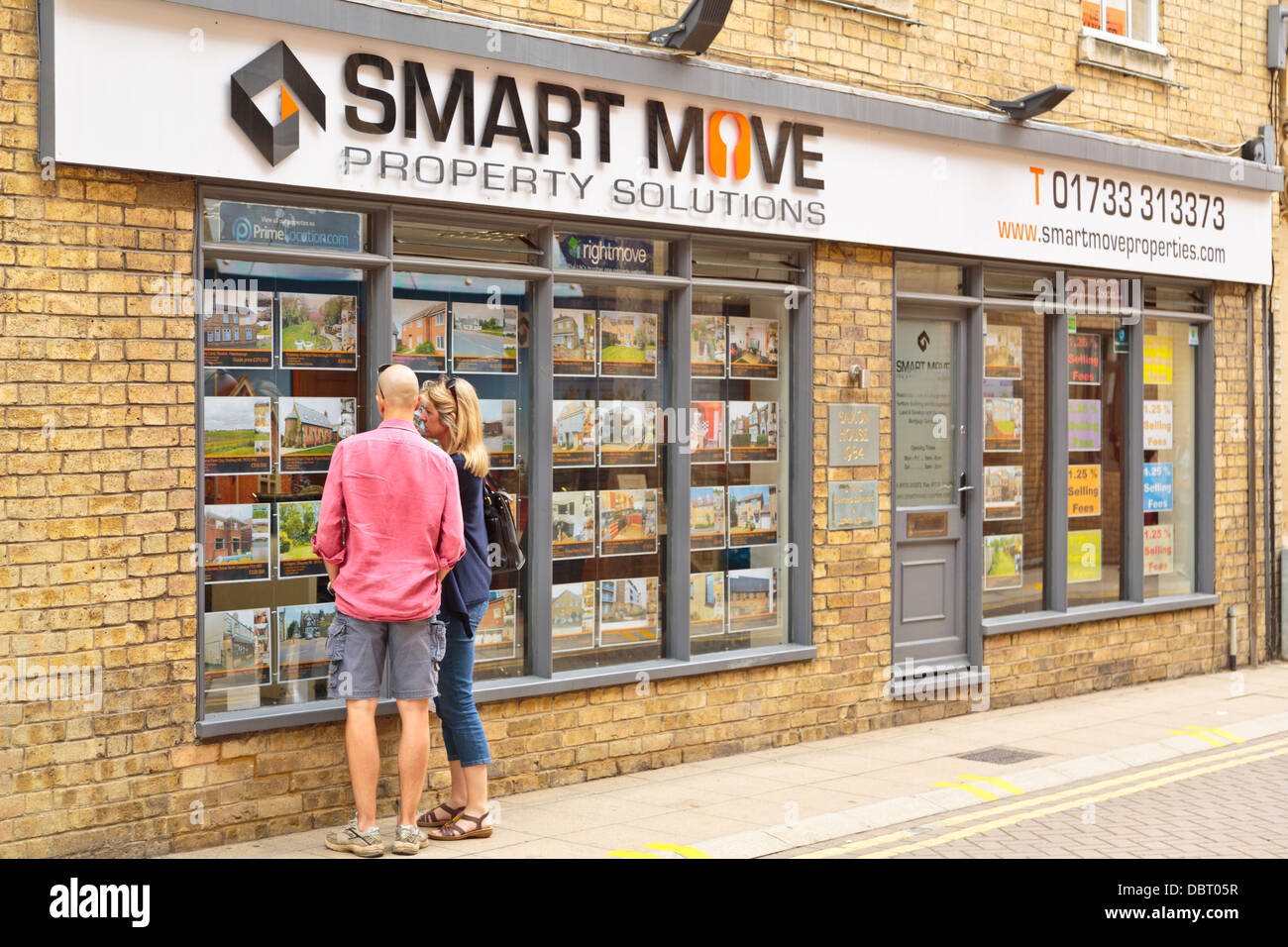 Couple looking at properties for sale or rent at an estate agent shop window, Peterborough, England - Stock Image