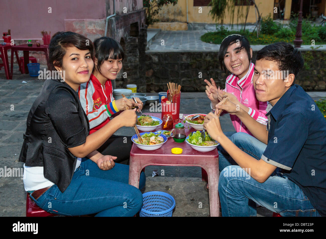 Four young people eating at an outdoor sidewalk cafe in Hoi An, Vietnam, Asia. - Stock Image