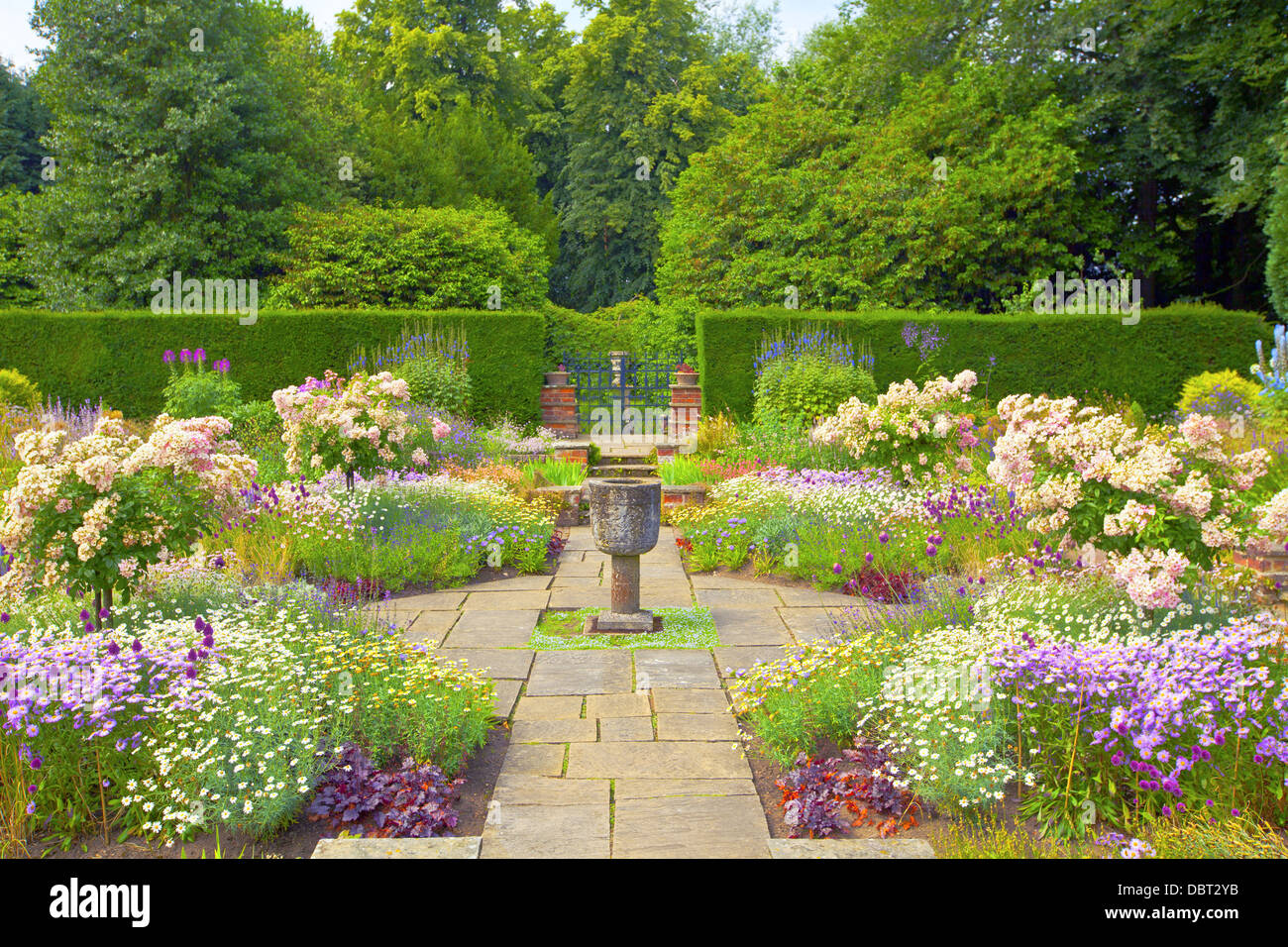 Flagged English summer garden with stone vase ornament. Stock Photo