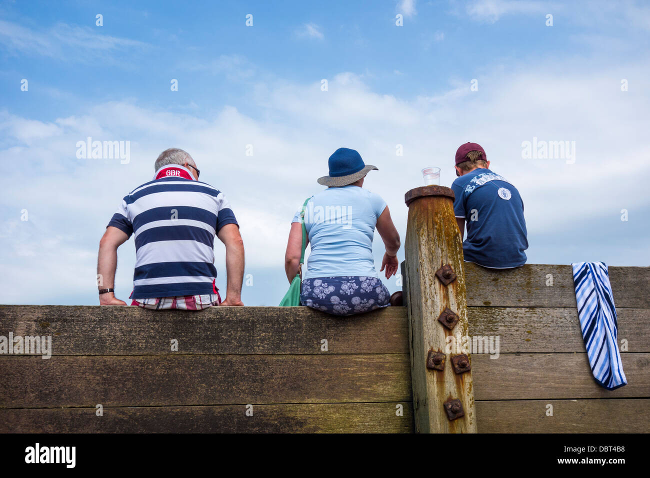 Seaside Holiday Grandparents and Grandson Sitting on a Groyne Whitstable Stock Photo