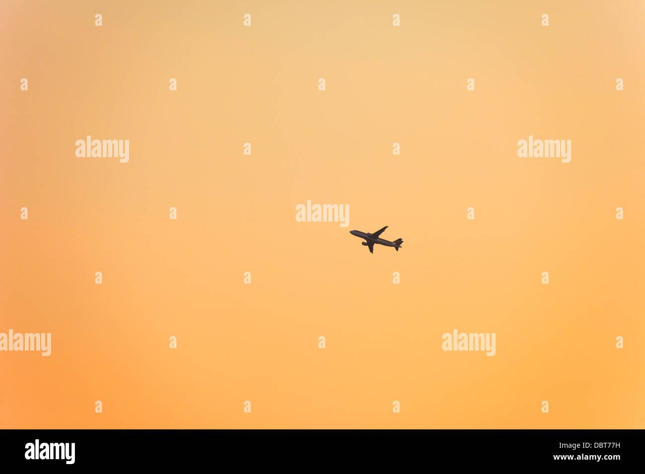 Silhouette of airplane on orange sky - Stock Image