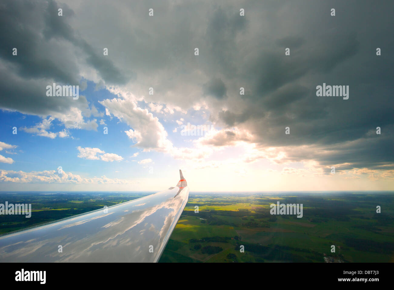 Clouds reflecting in airplane wing - Stock Image