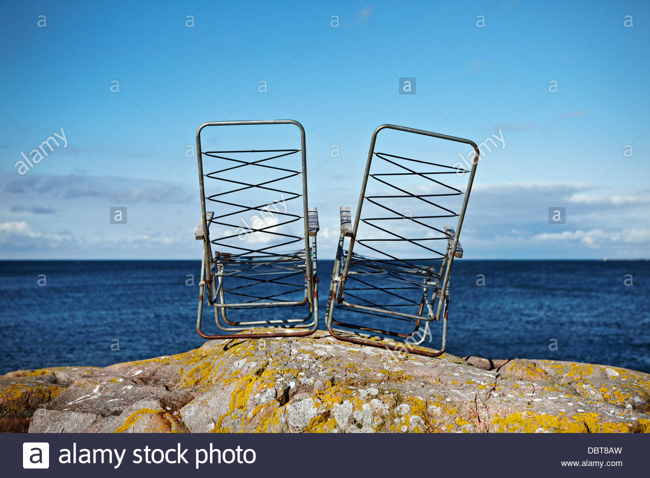 Two damaged deck chairs on rock near sea - Stock Image