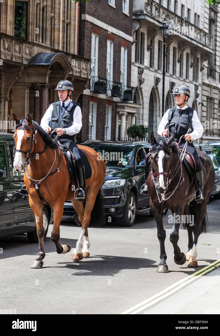Two mounted British Metropolitan police officers on patrol, Great George Street, London, England, UK. - Stock Image