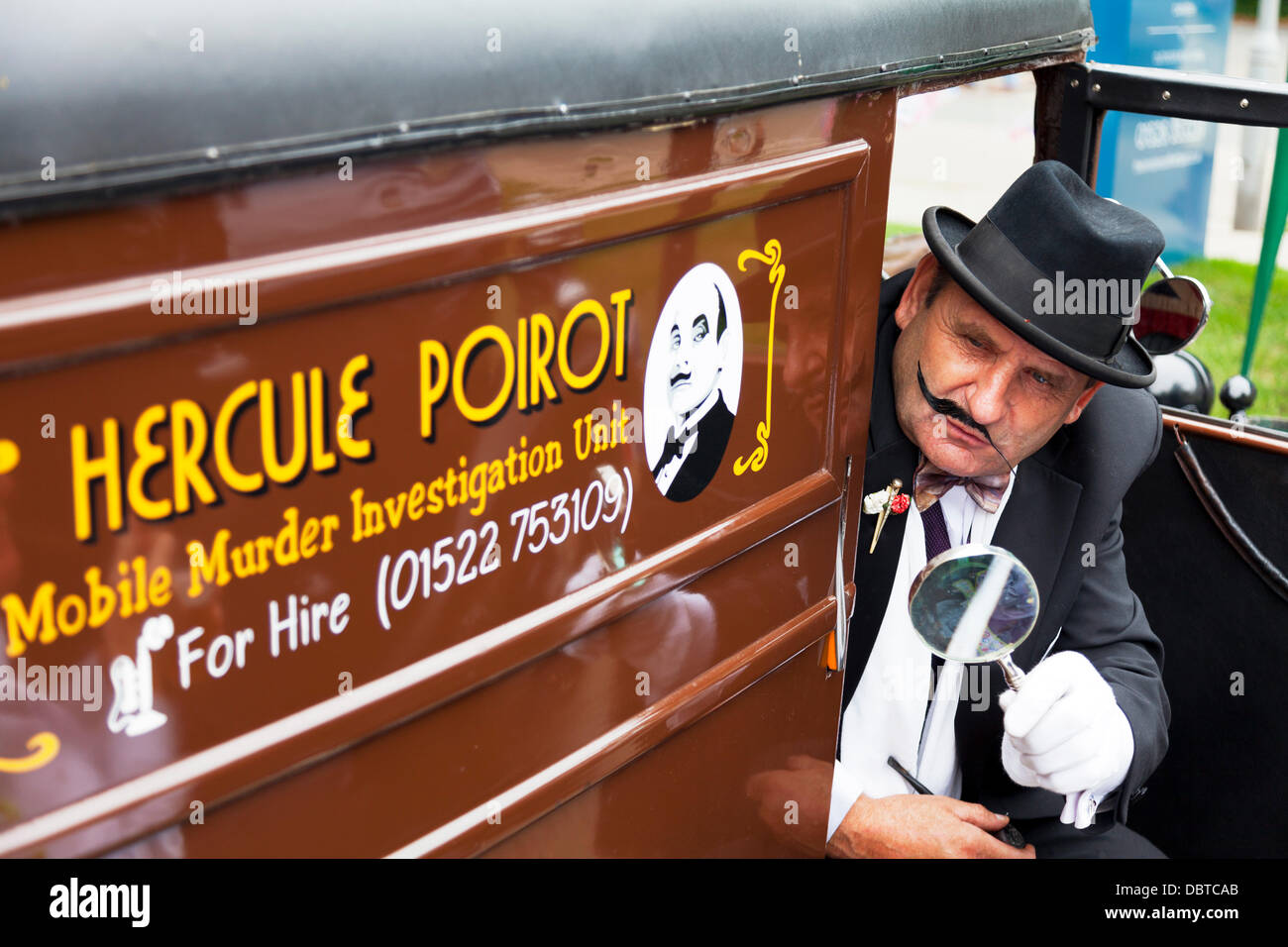 Man dressed in traditional 1940's outfit of Hercule Poirot investigator in vehicle with mustache and suit Credit: - Stock Image