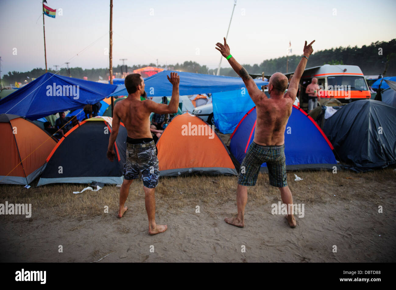 Two men having fun and cheering at the main campsite during the Przystanek Woodstock Music festival in Kostrzyn, - Stock Image