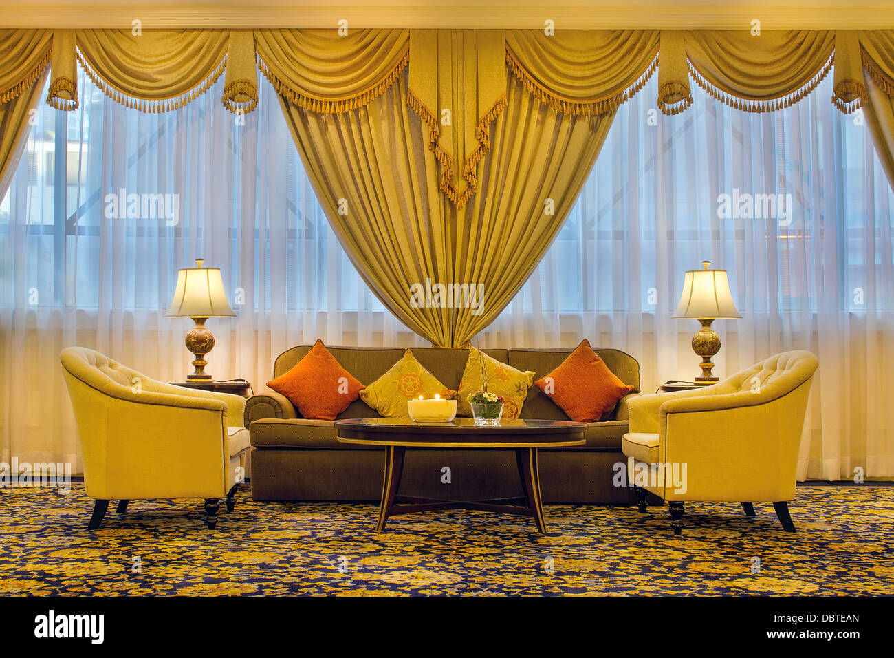 Living Room With Ornate Curtains Chairs Couch Side Table Lamps