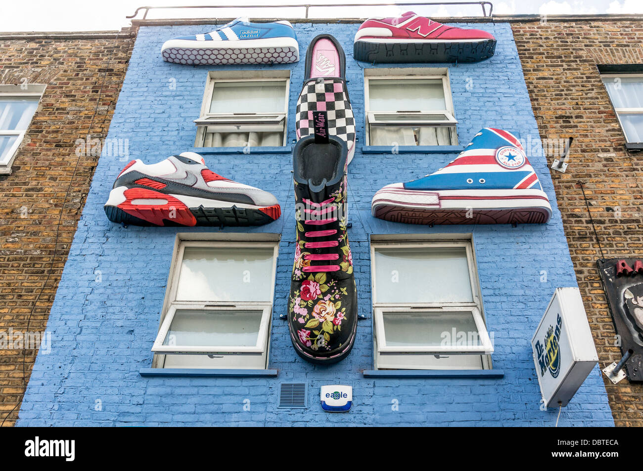Giant footwear on the wall above a footwear store on Camden high street, near Camden Market, London, England, UK. - Stock Image