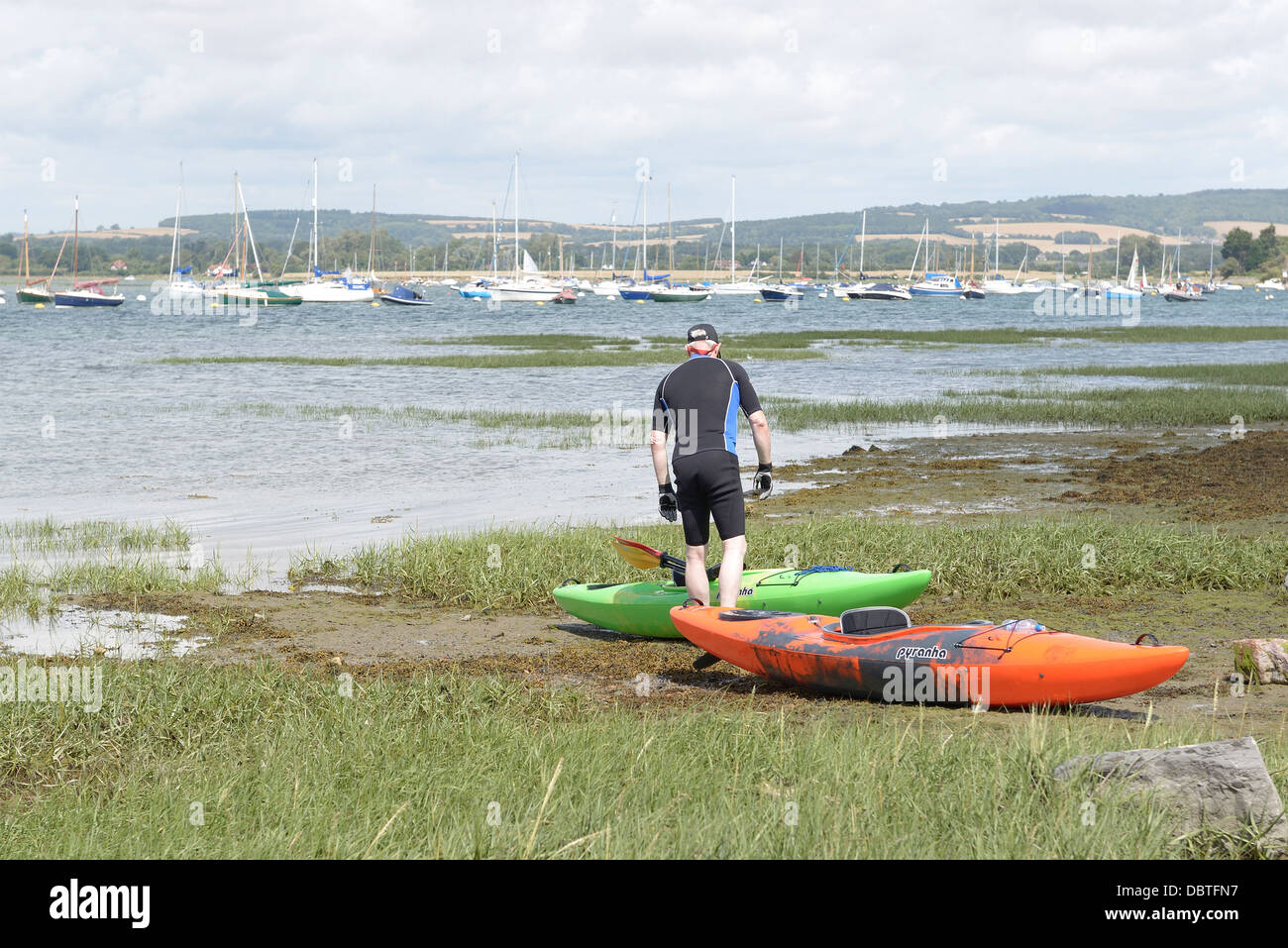 man on the harbour foreshore at bosham standing with his kayak whilst the tide is coming in - Stock Image