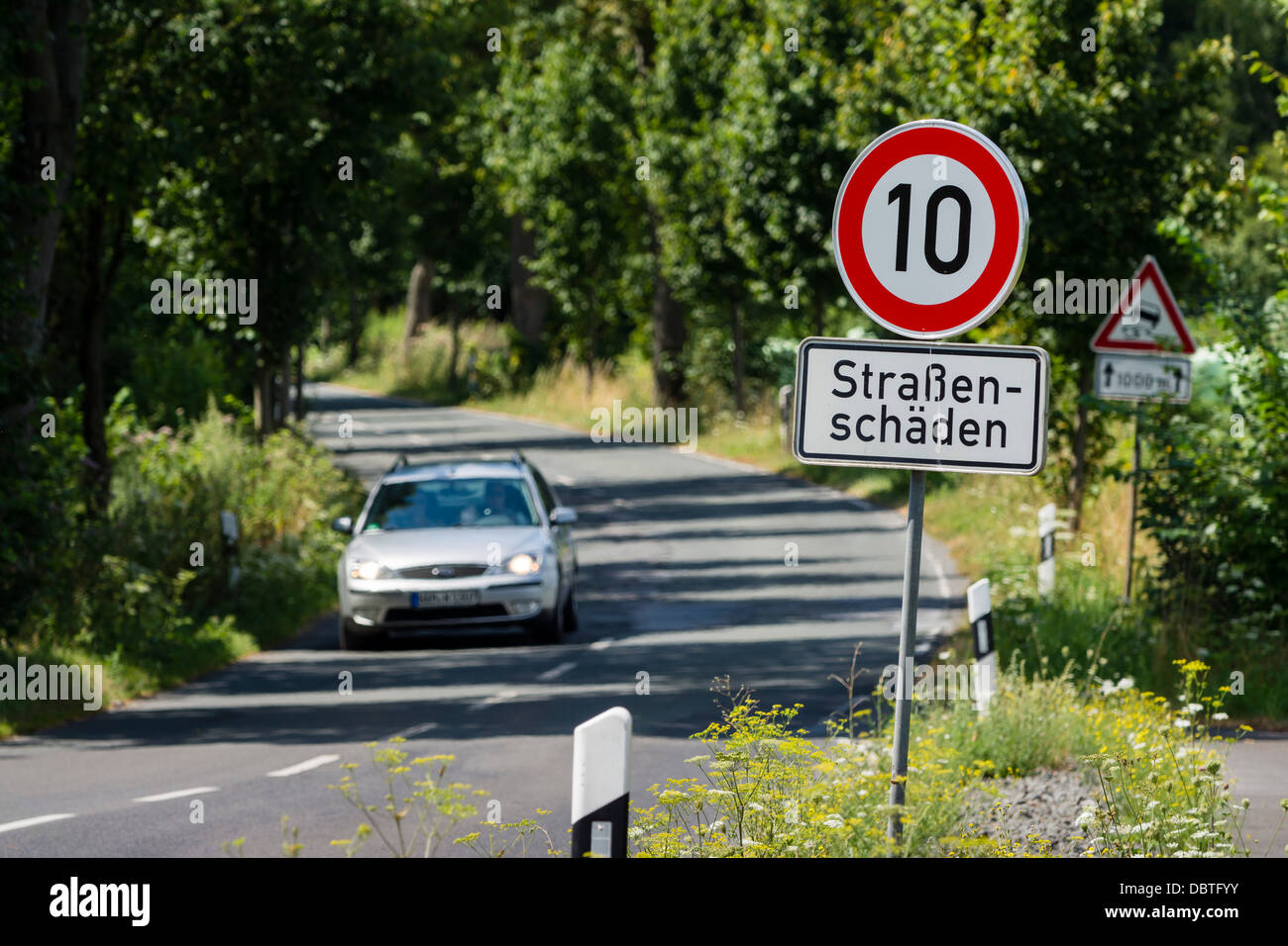 A car drives on the L657 road between Dortmund-Mengede and Castrop-Rauxel. Due to roadway damage, the speed limit - Stock Image