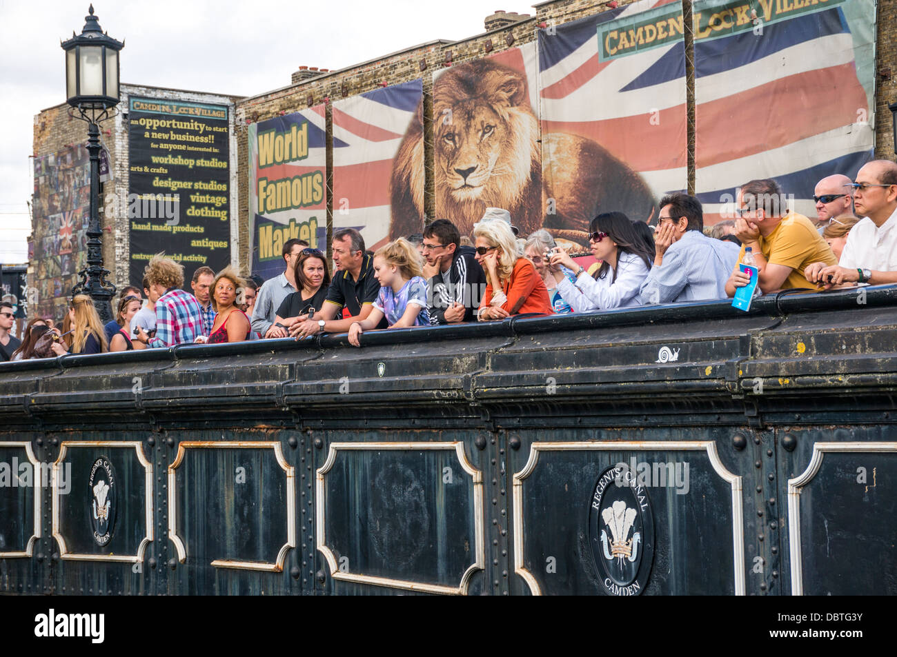 Sightseers on the Regents Canal bridge at Camden Lock, with a huge Union Jack and lion poster behind them, London, - Stock Image