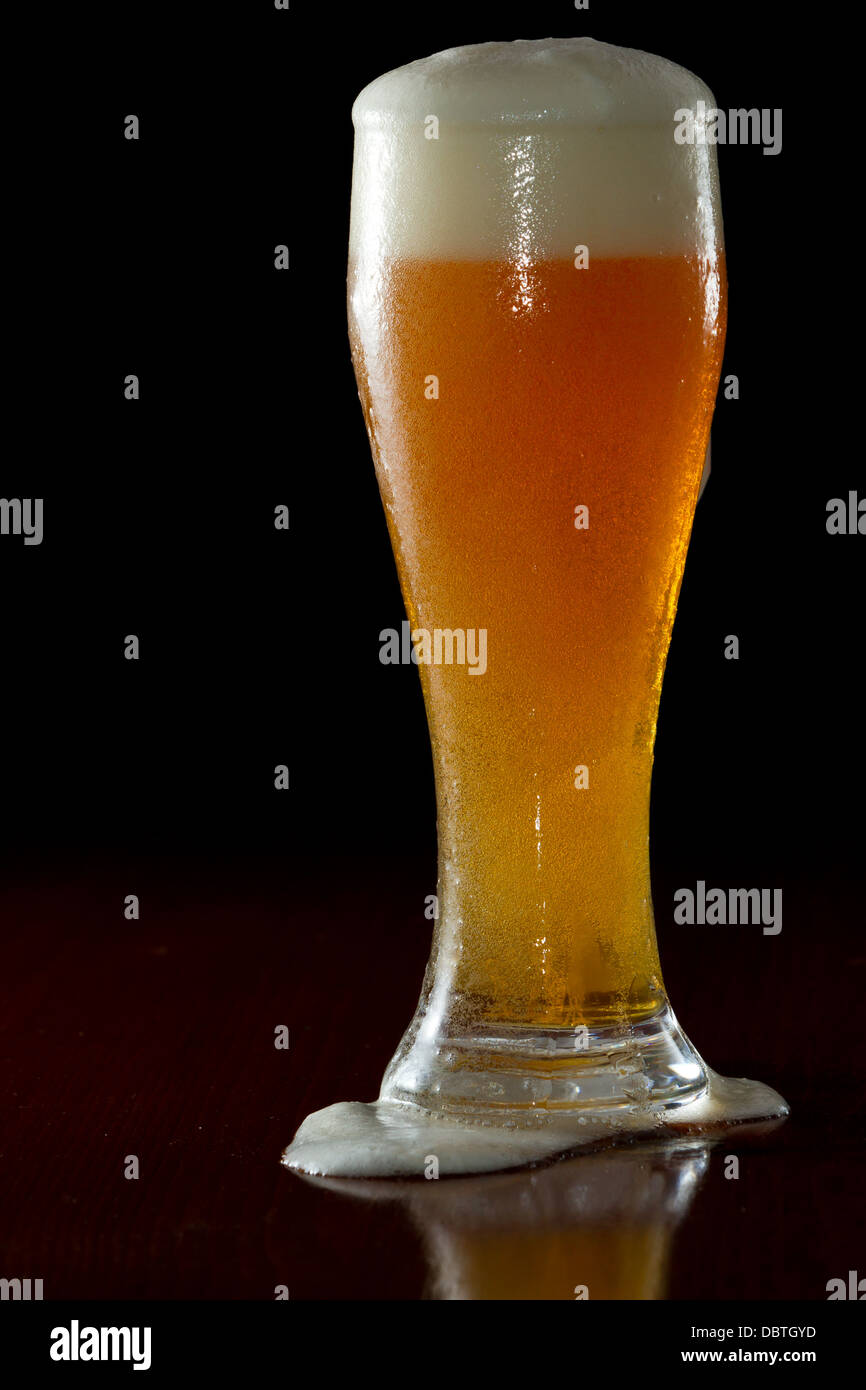beer served in a chilled glass on a dark bar Stock Photo
