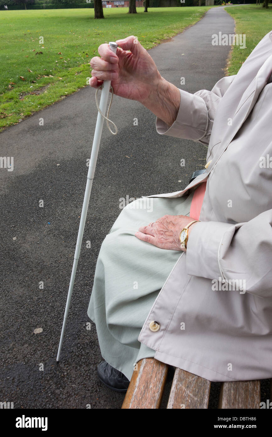 Ninety year old visually impaired lady with white stick sitting on bench in public park. England, UK - Stock Image