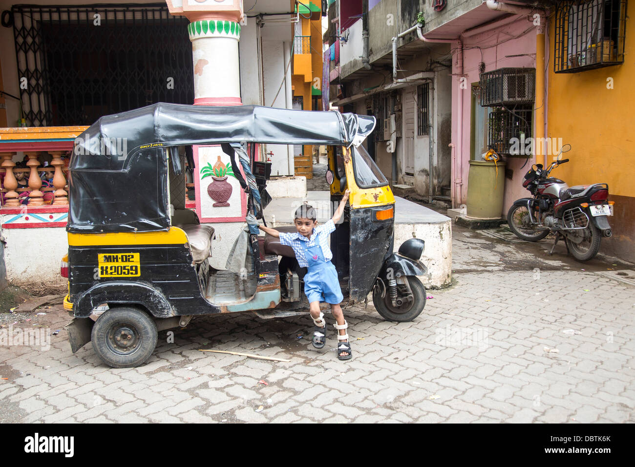 Small Indian boy plays on autorickshaw crippled leg braces - Stock Image