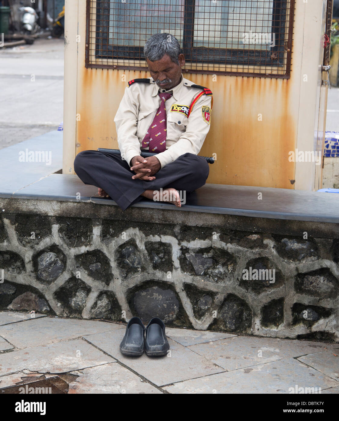 Seafront guard asleep on job snoozing  shoes off - Stock Image