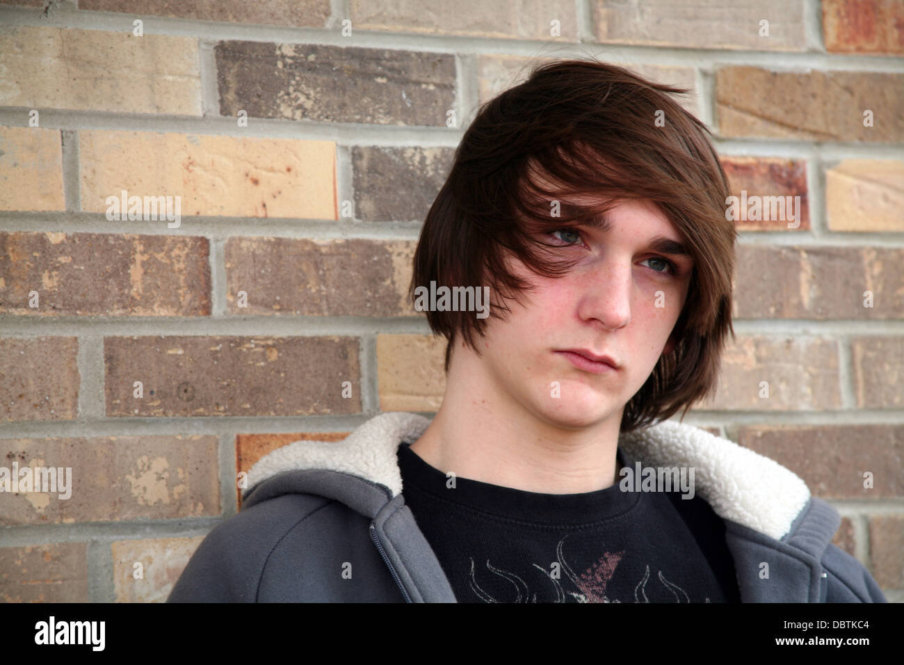 cute teen boy with great hair by brick wall Stock Photo - Alamy