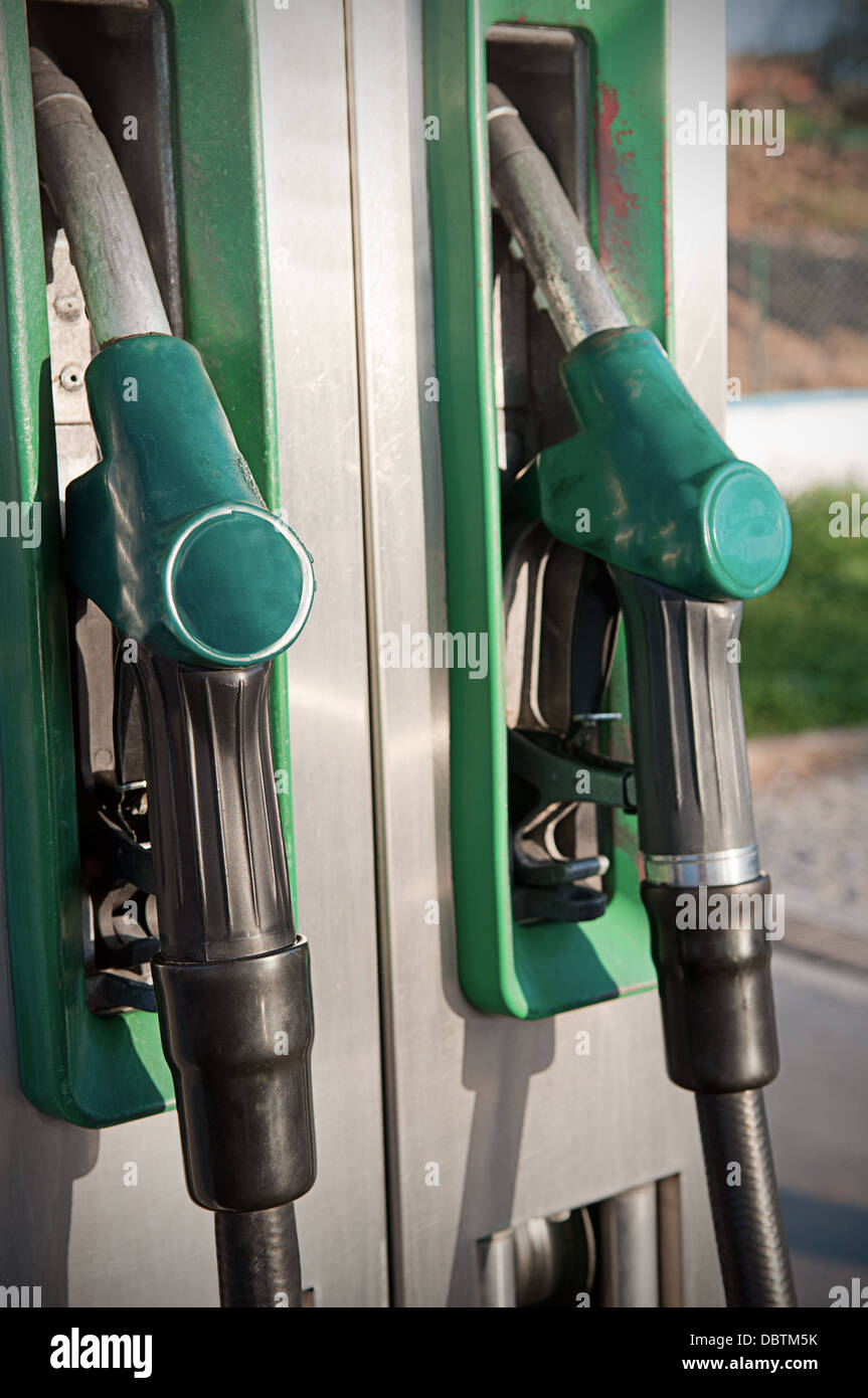 Closeup of fuel nozzles at a gas station. Gritty look. - Stock Image